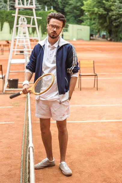 handsome old-fashioned tennis player with racket on brown court near tennis net - Photo, Image