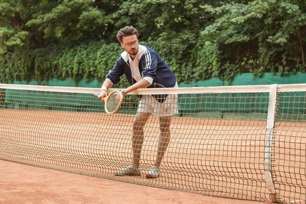 handsome tennis player with racket leaning on tennis net on brown court - Photo, Image
