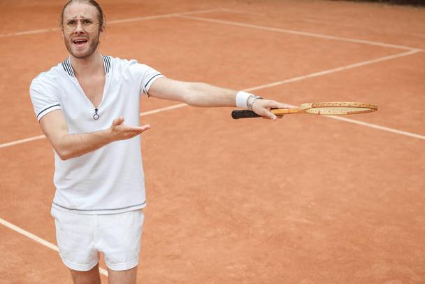 tenista emocional preocupado apontando com raquete no campo de ténis  - Foto, Imagem