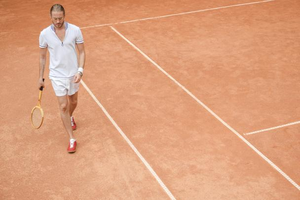 handsome sportsman with tennis racket walking on brown court - Photo, Image