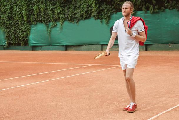handsome man in sportswear with retro wooden racket on tennis court - Photo, Image