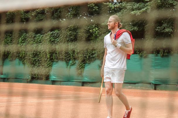 selective focus of tennis player with racket through net - Photo, Image