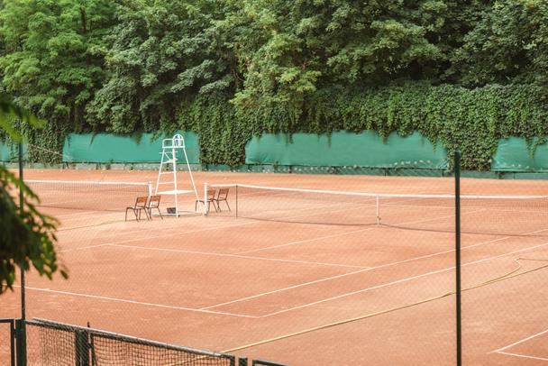 view of brown tennis court with net, chairs and trees  - Photo, Image
