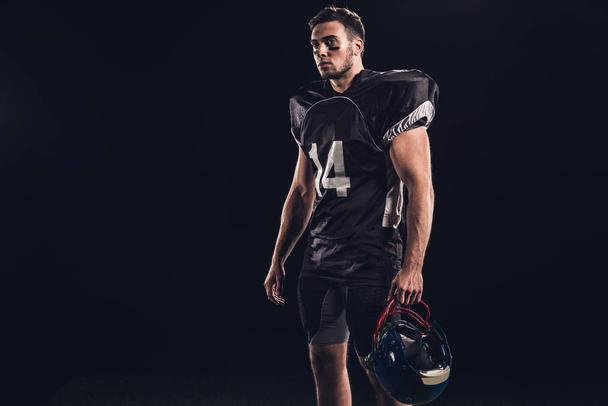 athletic american football player in black uniform isolated on black - Photo, Image