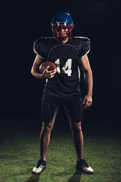 confident american football player holding ball in hand and looking at camera isolated on black - Photo, Image
