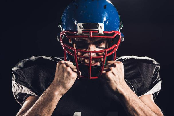 close-up portrait of angry american football player in helmet looking at camera isolated on black - Photo, Image