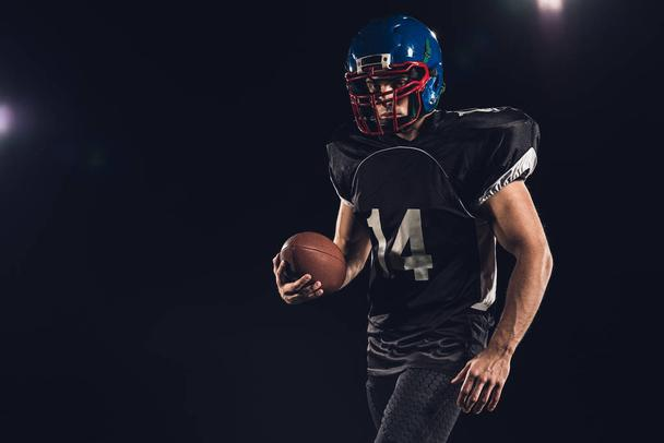 equipped american football player with ball isolated on black - Photo, Image