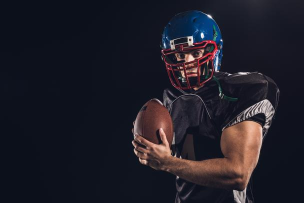 american football player with ball looking at camera isolated on black - Photo, Image