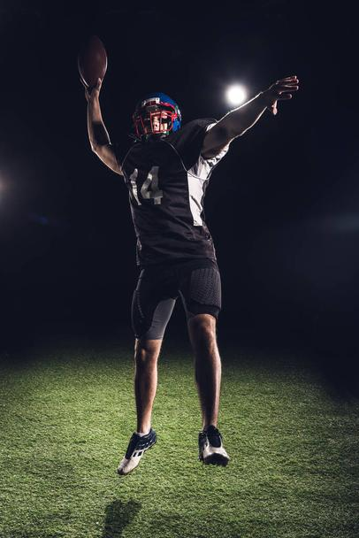 athletic american football player jumping with ball under spotlights on black - Photo, Image