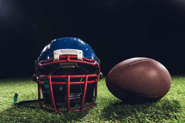 close-up shot of american football helmet with ball on green grass on black - Photo, Image