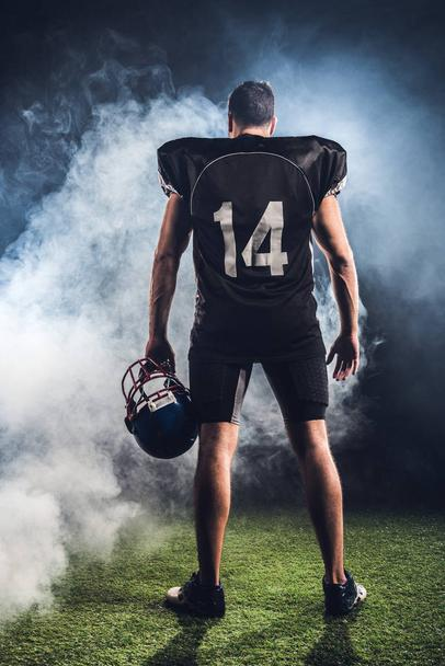 rear view of equipped american football player with helmet in hand against white smoke - Photo, Image