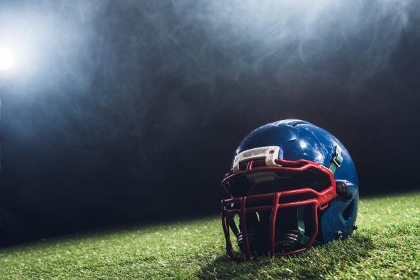 close-up shot of american football helmet on green grass with white smoke above - Photo, Image