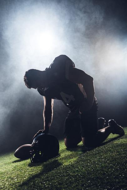 sad failed american football player standing on knees on green grass and looking down against white smoke - Photo, Image