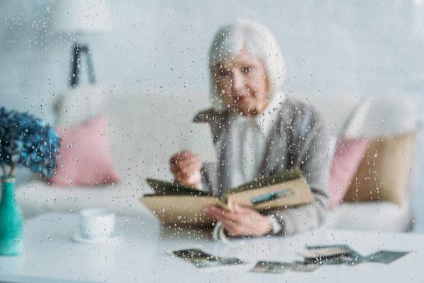 Selektiver Fokus der Seniorin beim Betrachten von Fotos im Fotoalbum am Tisch mit einer Tasse Kaffee zu Hause - Foto, Bild