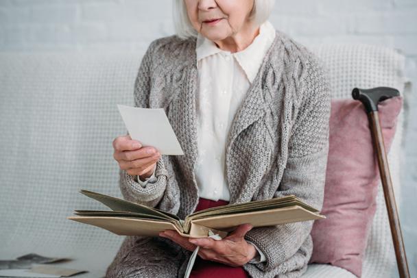Schnappschuss von Seniorin mit Fotoalbum, die zu Hause auf Couch sitzt - Foto, Bild