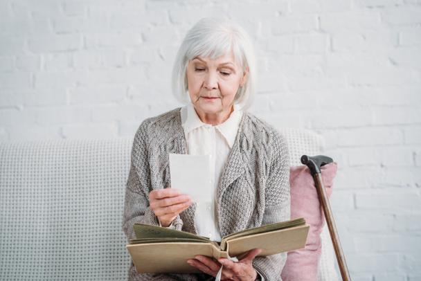 Porträt einer Dame mit grauen Haaren, die Fotos aus dem Fotoalbum betrachtet, während sie zu Hause auf der Couch liegt - Foto, Bild