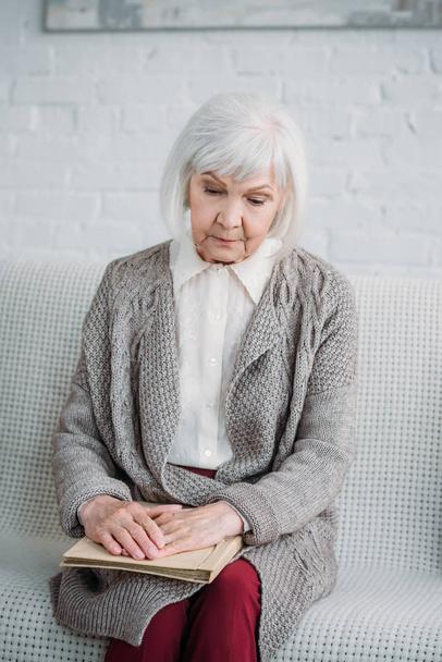 Porträt einer nachdenklichen Seniorin mit Fotoalbum auf Couch zu Hause - Foto, Bild
