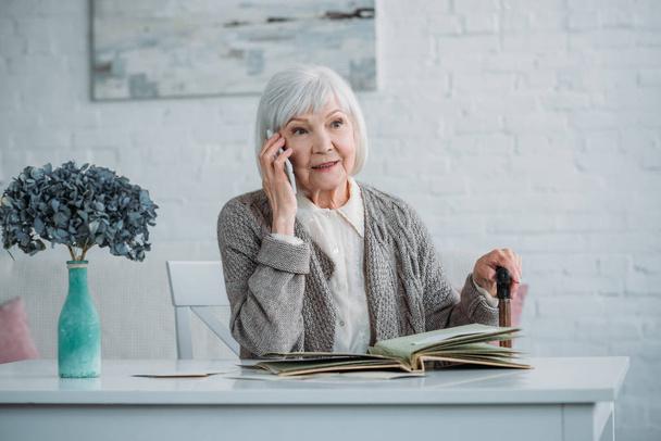 Porträt einer Seniorin mit Gehstock, die am Smartphone spricht, während sie zu Hause mit Fotoalbum am Tisch sitzt - Foto, Bild