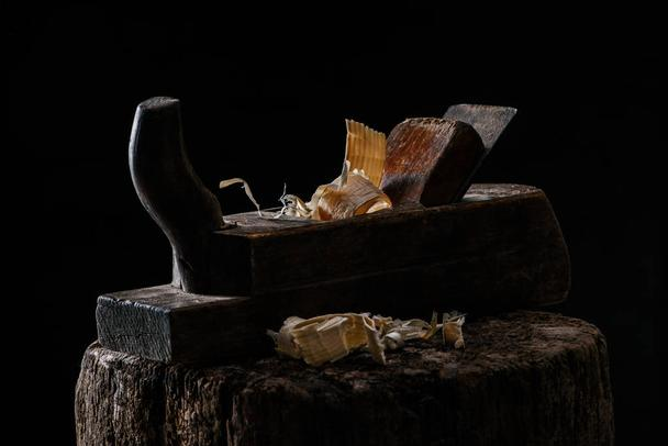 close up view of vintage woodworker plane on wooden stump isolated on black - Photo, Image
