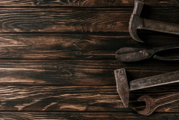 top view of arranged hammers, wrench and scissors vintage tools on wooden surface - Photo, Image