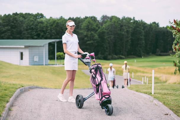 selective focus of cheerful female golf player in cap and white polo with golf gear at golf course - Photo, Image