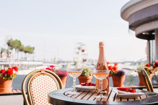 close-up view of two glasses of champagne, champagne bottle and sweet desserts on round table in outdoor cafe - Photo, Image