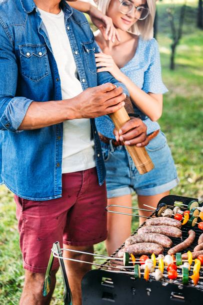 partial view of woman standing near african american boyfriend while he cooking food on grill - Photo, Image