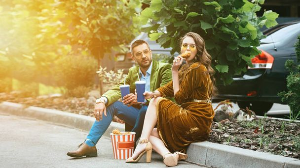fashionable couple in velvet clothing with drinks eating fried chicken legs on street - Photo, Image