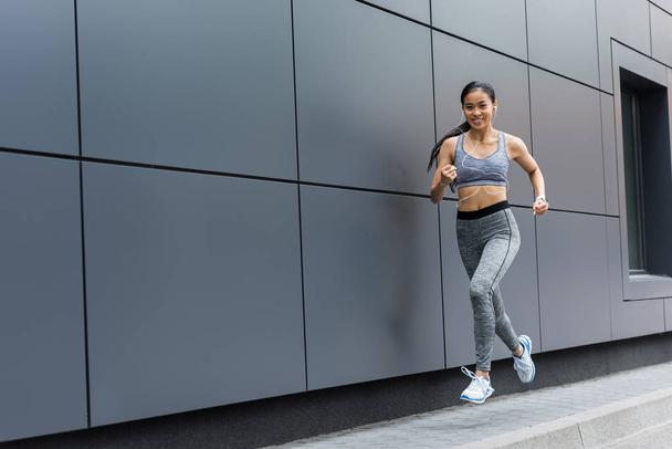 smiling young asian female athlete in earphones running at city street - Photo, Image