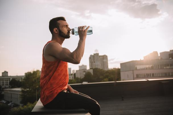 side view of handsome sportsman drinking water from sport bottle on roof - Photo, Image