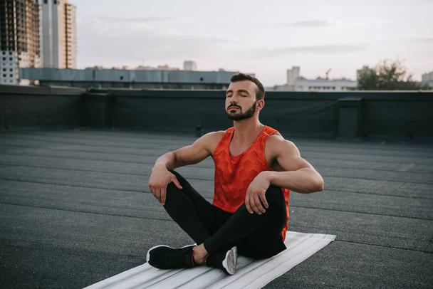 handsome sportsman stretching legs on yoga mat on roof - Photo, Image