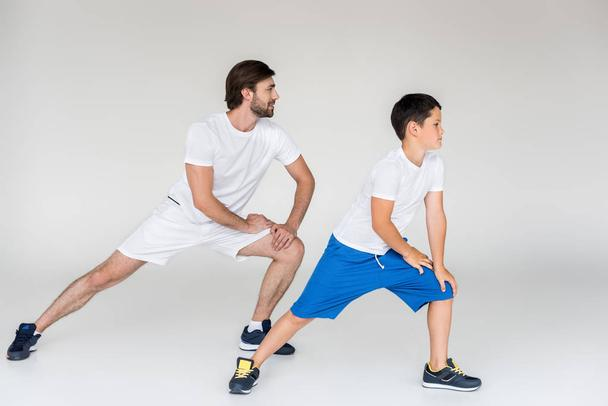 father and son in white shirts stretching on grey backdrop - Photo, Image
