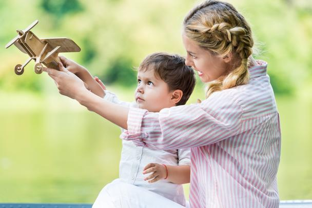happy mother with little son playing with toy plane at park - Photo, Image