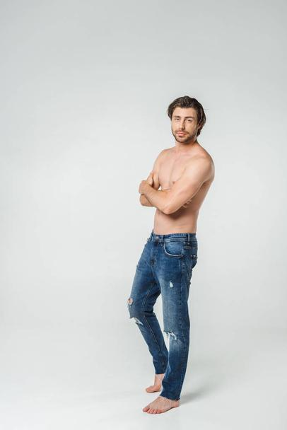 young shirtless man in jeans with arms crossed looking at camera on grey backdrop - Photo, Image