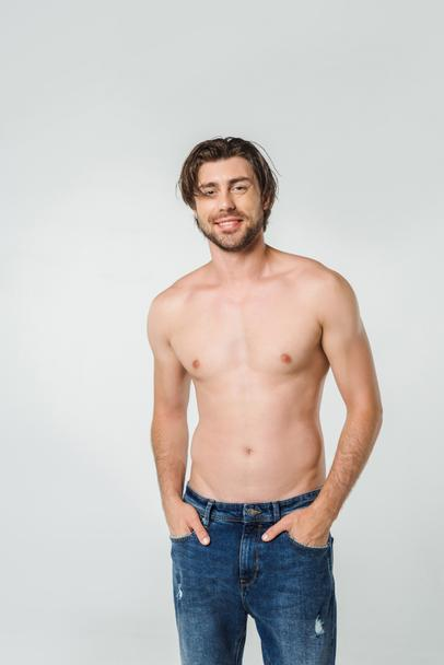 portrait of happy shirtless man in jeans isolated on grey - Photo, Image