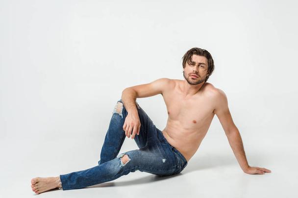 young shirtless man in jeans posing on grey backdrop - Photo, Image