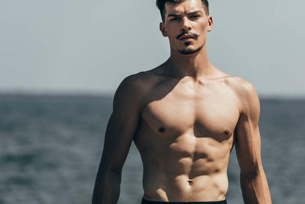 handsome athletic man looking at camera in front of sea - Photo, Image