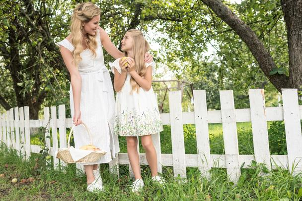 blonde mother and daughter with fruits in wicker basket posing near white fence in garden - Photo, Image