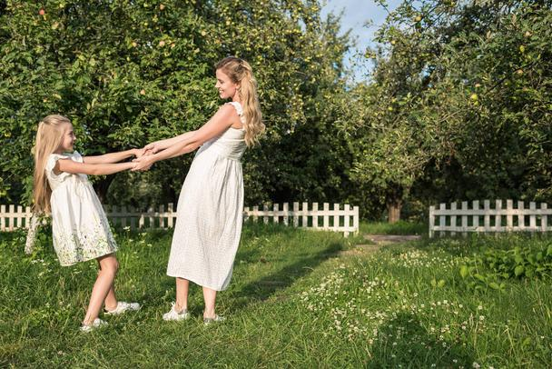 attractive mother and daughter in white dresses holding hands and twisting in orchard - Photo, Image