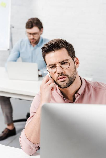 businessman working with computer and talking by phone at modern office with blurred colleague on background - Photo, Image