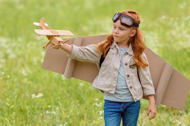 portrait of little child in pilot costume with wooden toy plane standing in meadow - Photo, Image