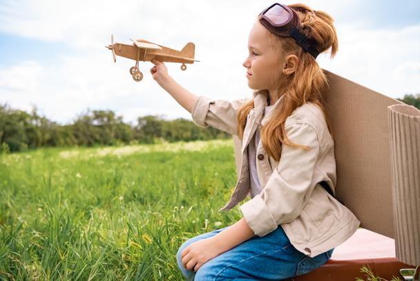 kid in pilot costume with wooden toy plane in hand sitting on retro suitcase in field - Photo, Image