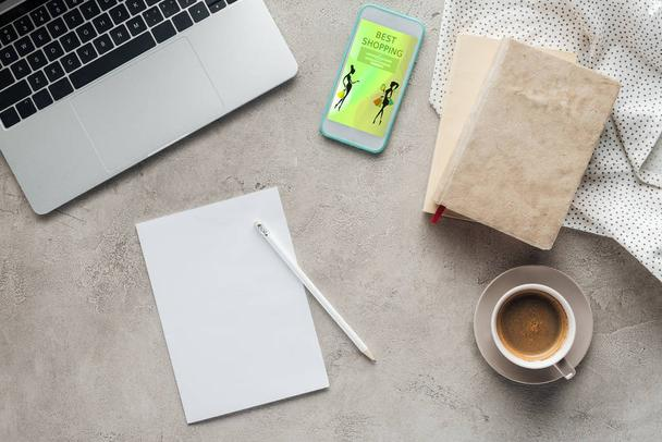 top view of coffee with laptop and smartphone with best shopping app on screen on concrete surface with blank paper - Photo, Image