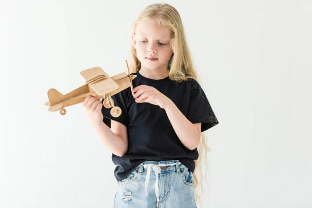 beautiful little kid playing with wooden toy plane isolated on white  - Photo, Image