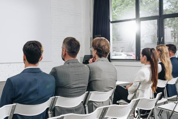 back view of businesspeople sitting on chairs during training in hub - Photo, Image