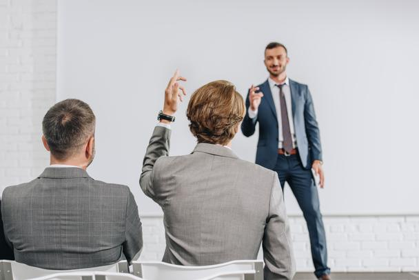 back view of businessman rising hand to coach during training in hub - Photo, Image