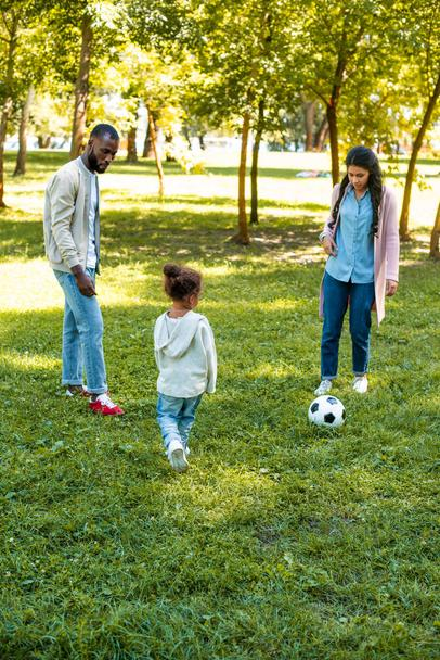 african american parents and daughter playing football together in park - Photo, Image