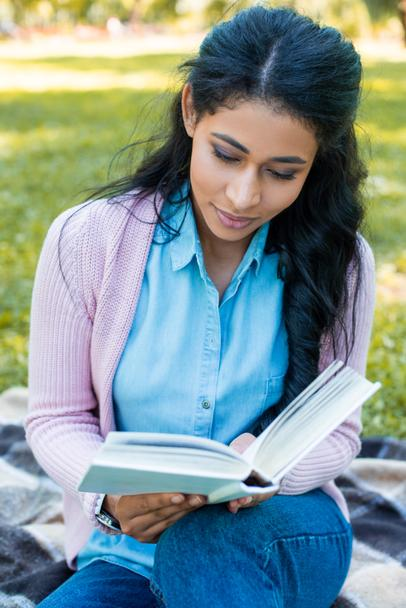attractive african american woman reading book in park - Photo, Image