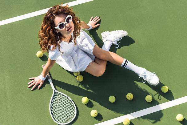 overhead view of fashionable tennis player in white sportswear and sunglasses resting on tennis court with balls and racket near by - Photo, Image