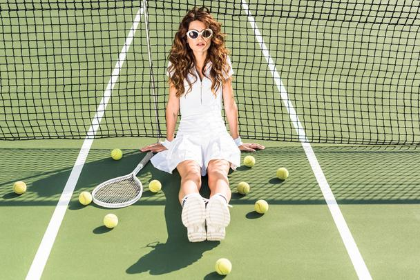 young fashionable tennis player in white sportswear and sunglasses sitting at net with tennis equipment around on tennis court - Photo, Image